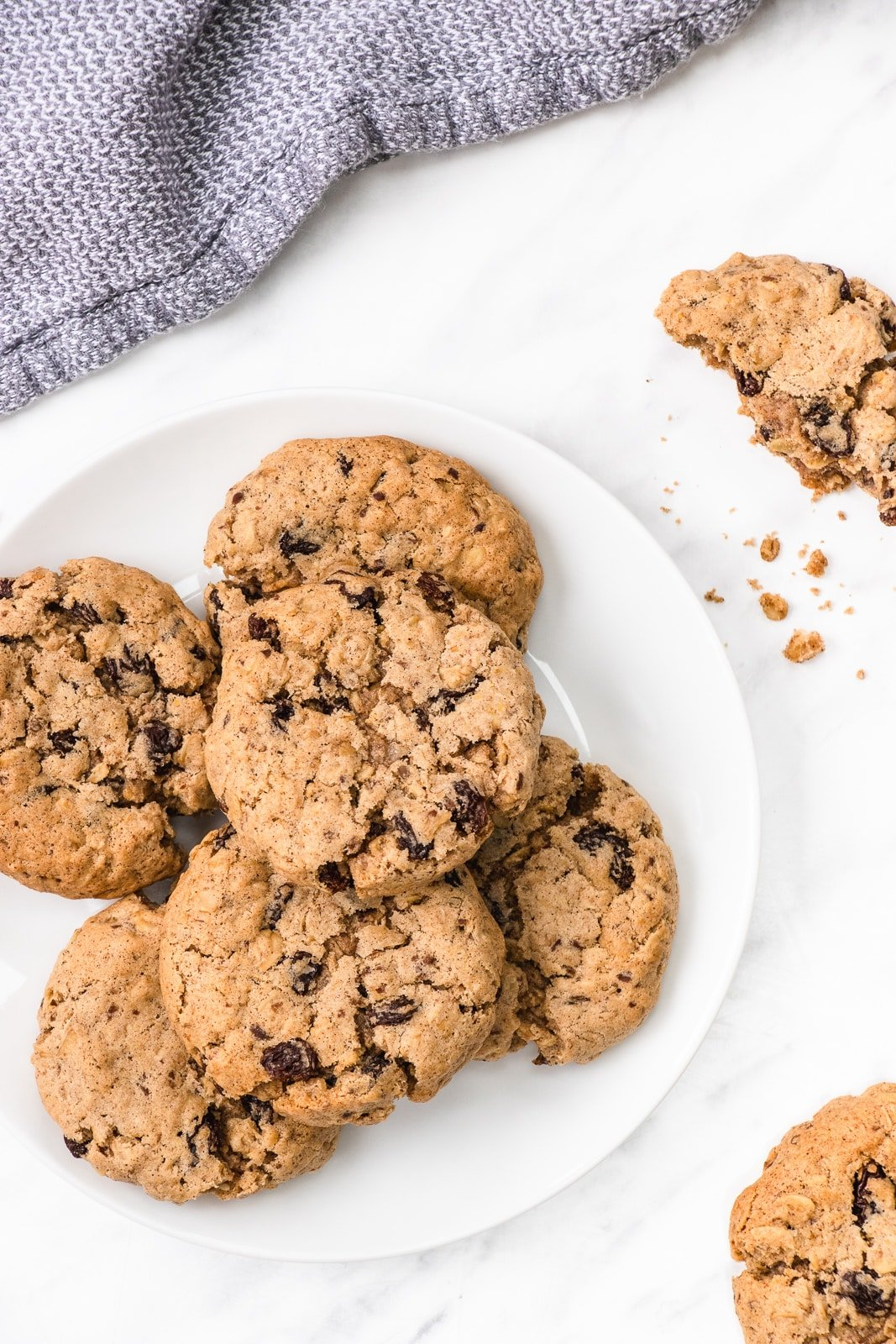 A stack of oatmeal raisin cookies on a round white plate surrounded by more cookies and some crumbs
