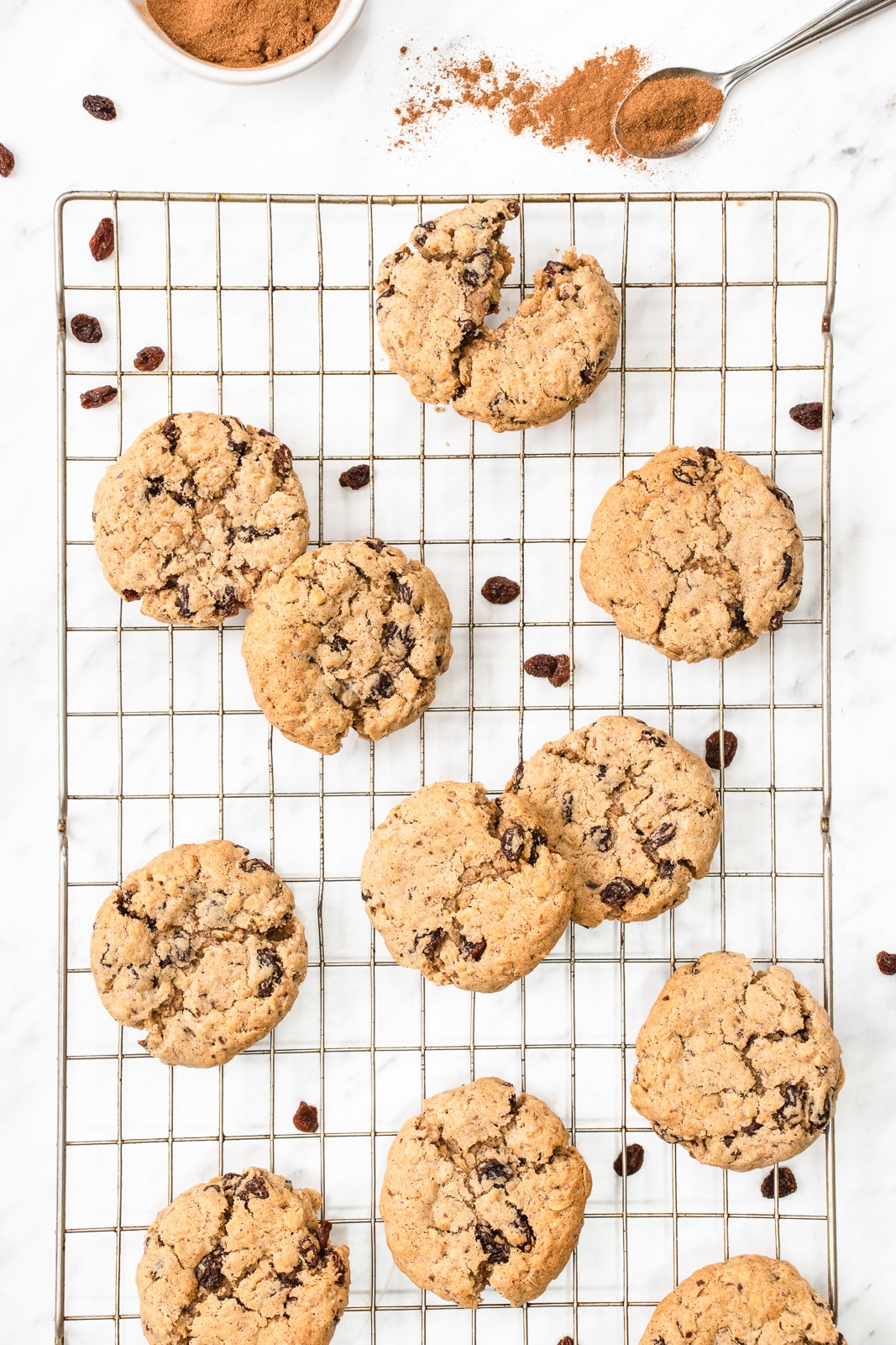 10 oatmeal raisin cookies on a cooling rack next to a pile of cinnamon