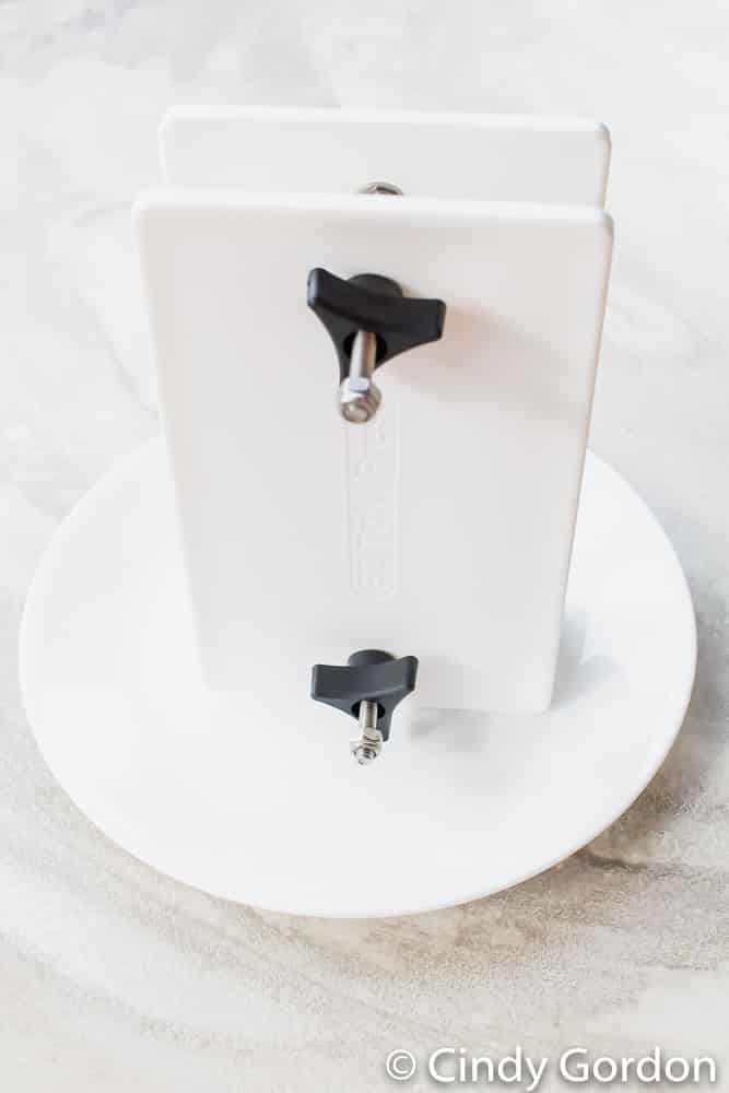 An EZ Tofu Press standing up on a round white plate to drain tofu