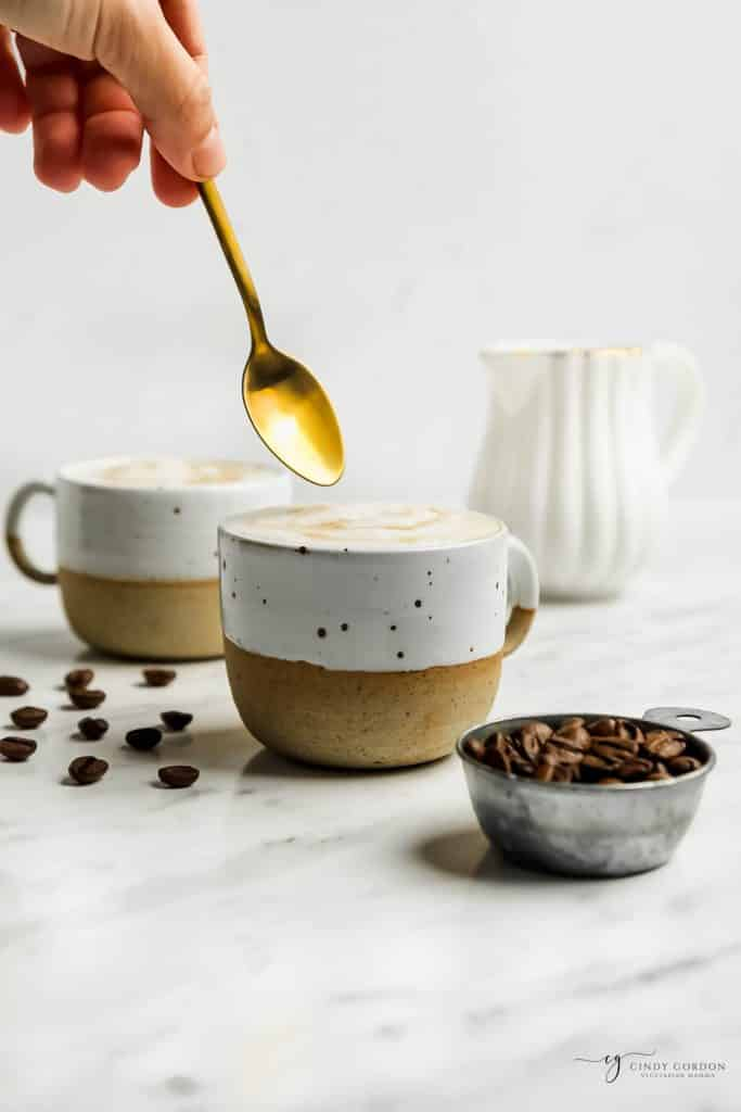 golden spoon being dipped into a white frothy liquid in a white and gold mug