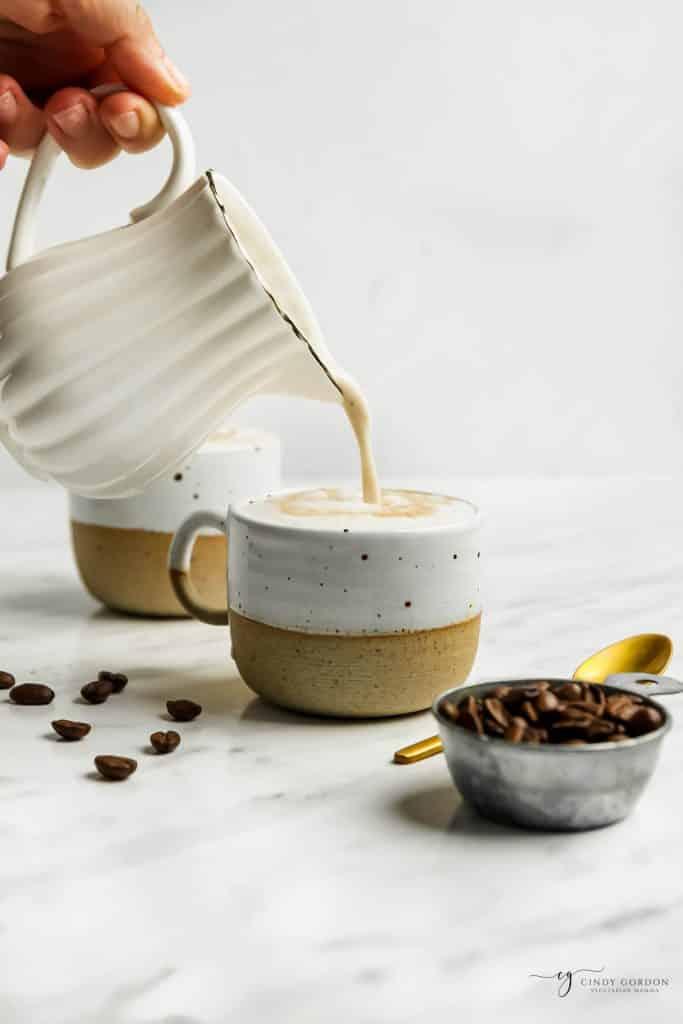 white pitcher pouring out oat milk lattes into a white ceramic mug