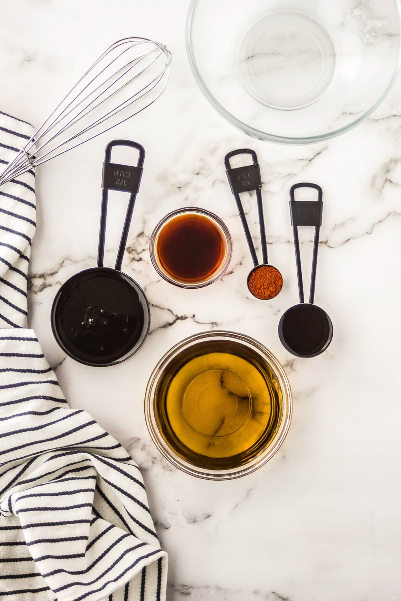 A bowl of oil next to measuring cups of cayenne pepper, Worcestershire sauce, maple syrup, and liquid smoke
