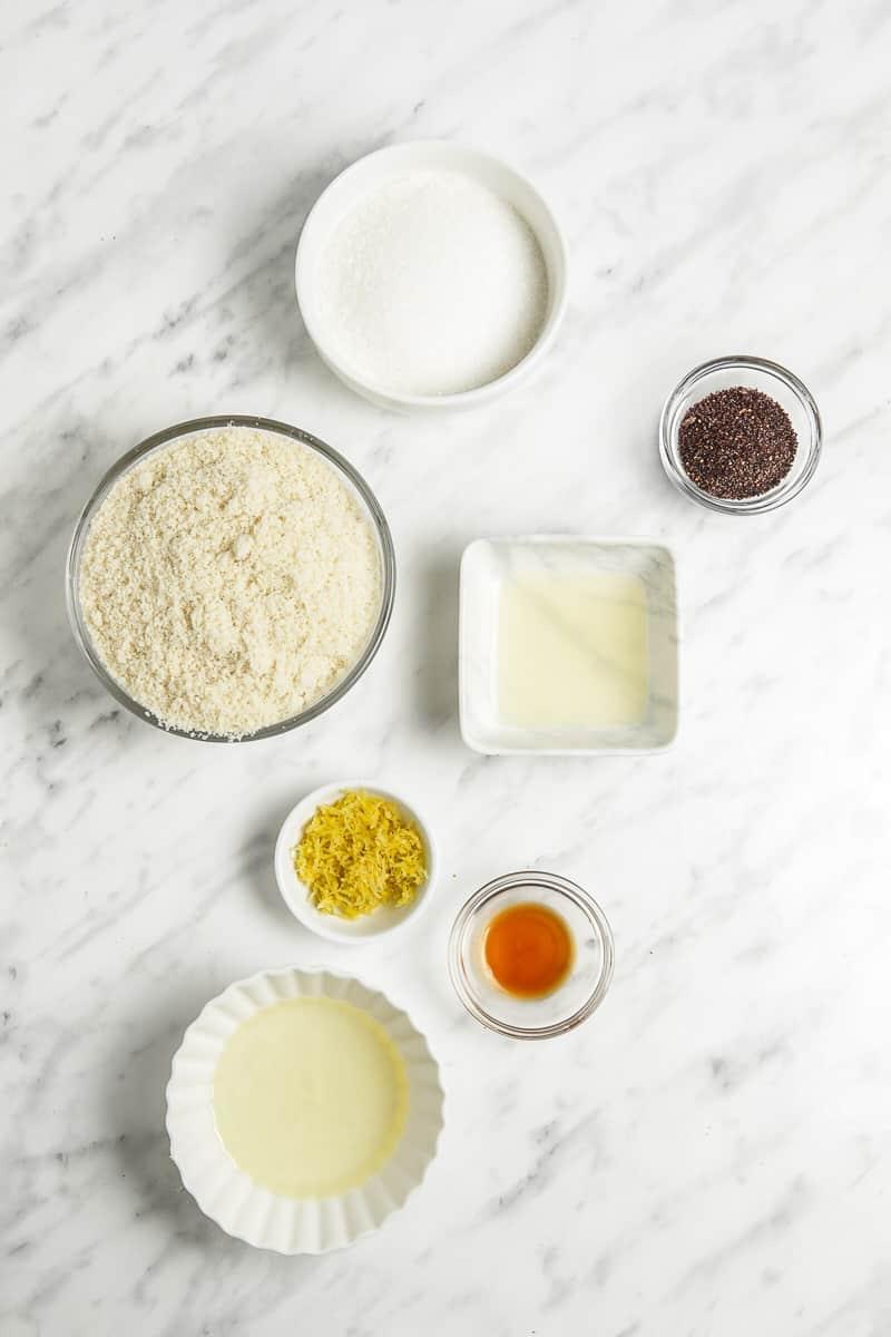 Bowls of almond flour, poppy seeds, vanilla extract, lemon juice, lemon zest, egg whites, and sugar