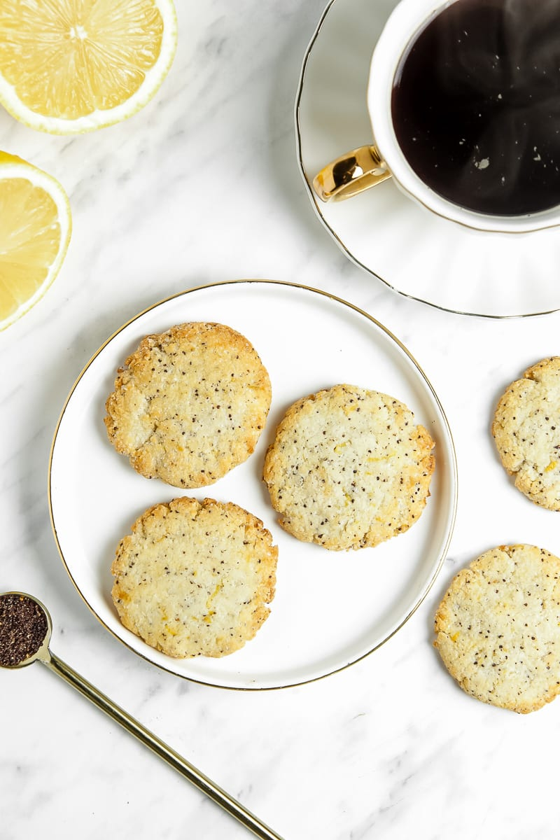 3 lemon poppy seed cookies on a gold and white plate next to a cup of coffee, more cookies, and lemon slices