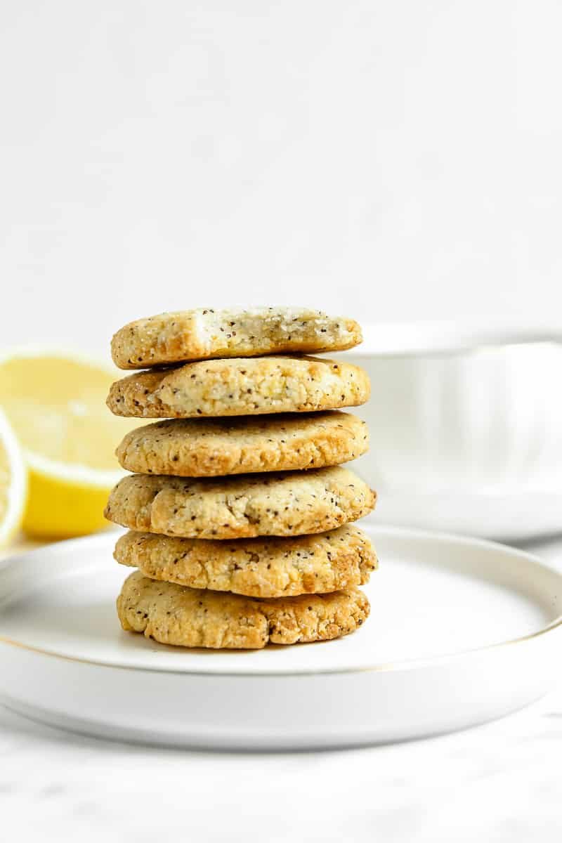 Six lemon poppy seed cookies in a tall stack on a white plate