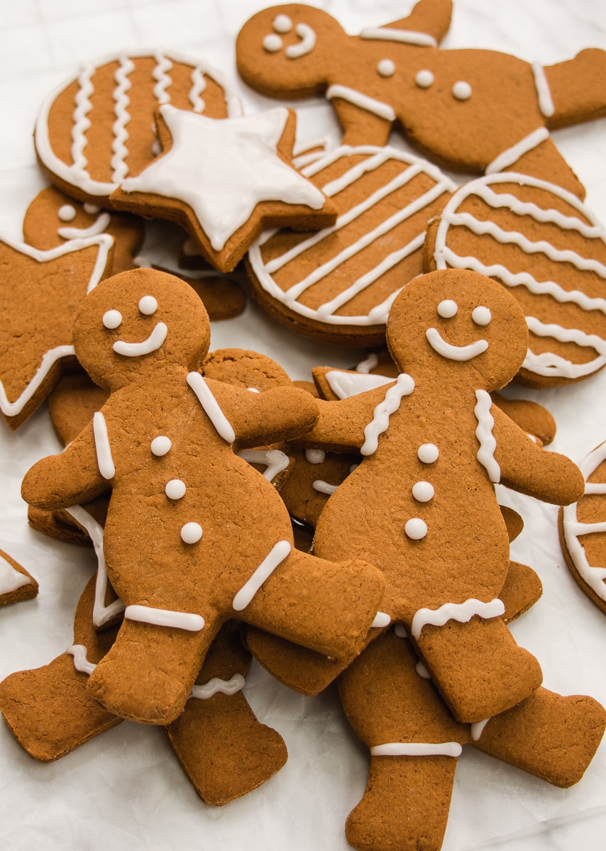 Close-up shot of 2 gingerbread people on a pile of more decorated gingerbread cookies