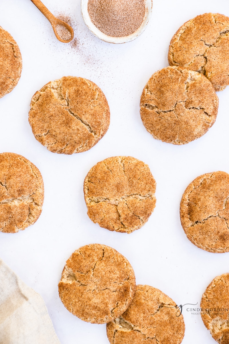 An array of snickerdoodle cookies on a white countertop next to a bowl and spoonful of cinnamon sugar