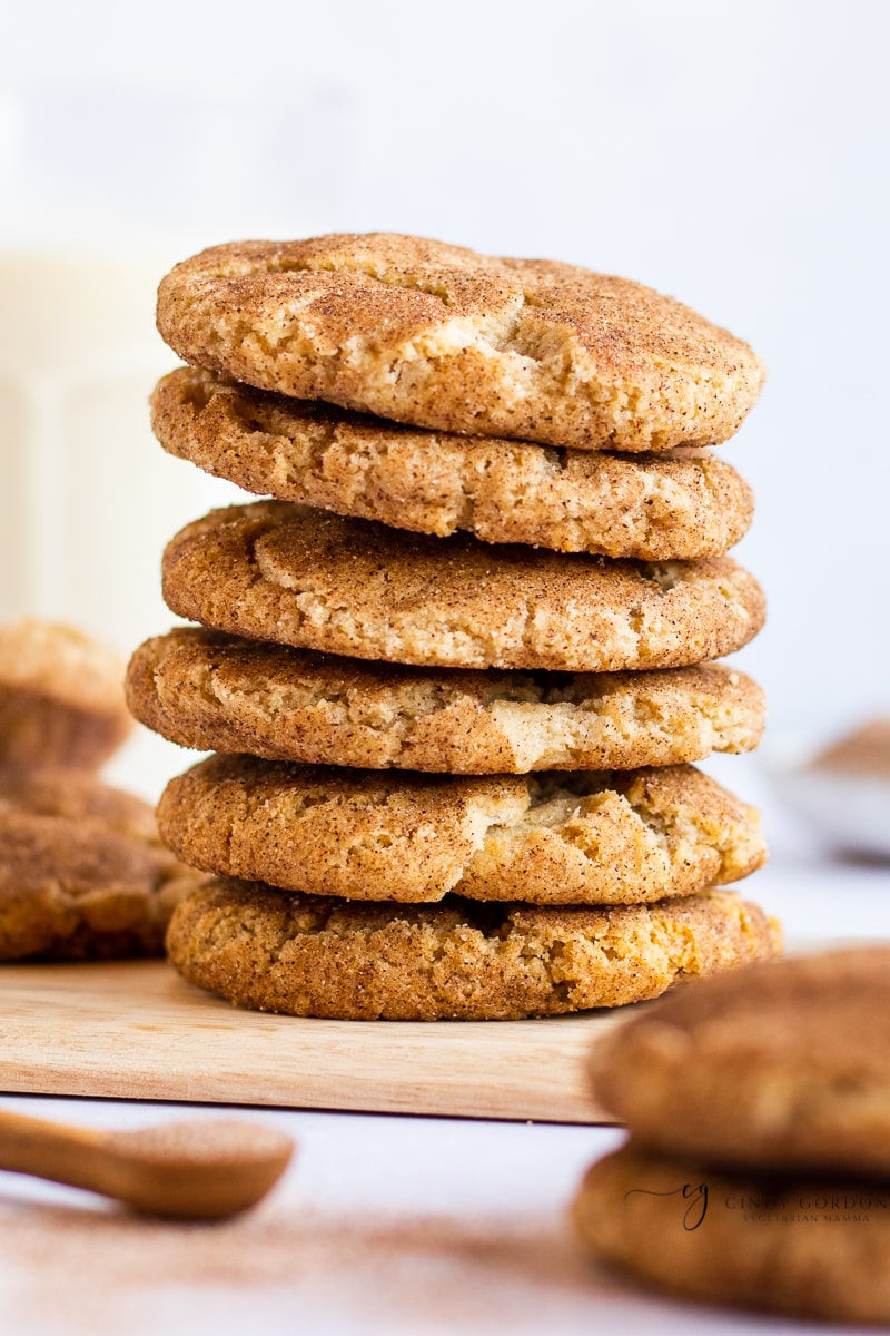 A stack of 6 snickerdoodle cookies on a wooden cutting board surrounded by more cookies