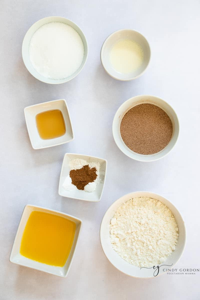 Bowls of sugar, almond milk, cinnamon, sugar, vanilla extract, almond flour, xanthan gum, cream of tartar, and vegan butter