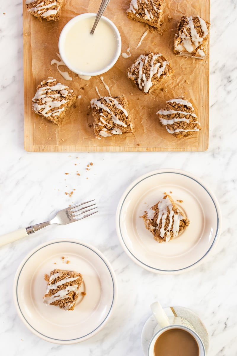 two plates of coffee cake next to a cutting board of more cake with a bowl of icing