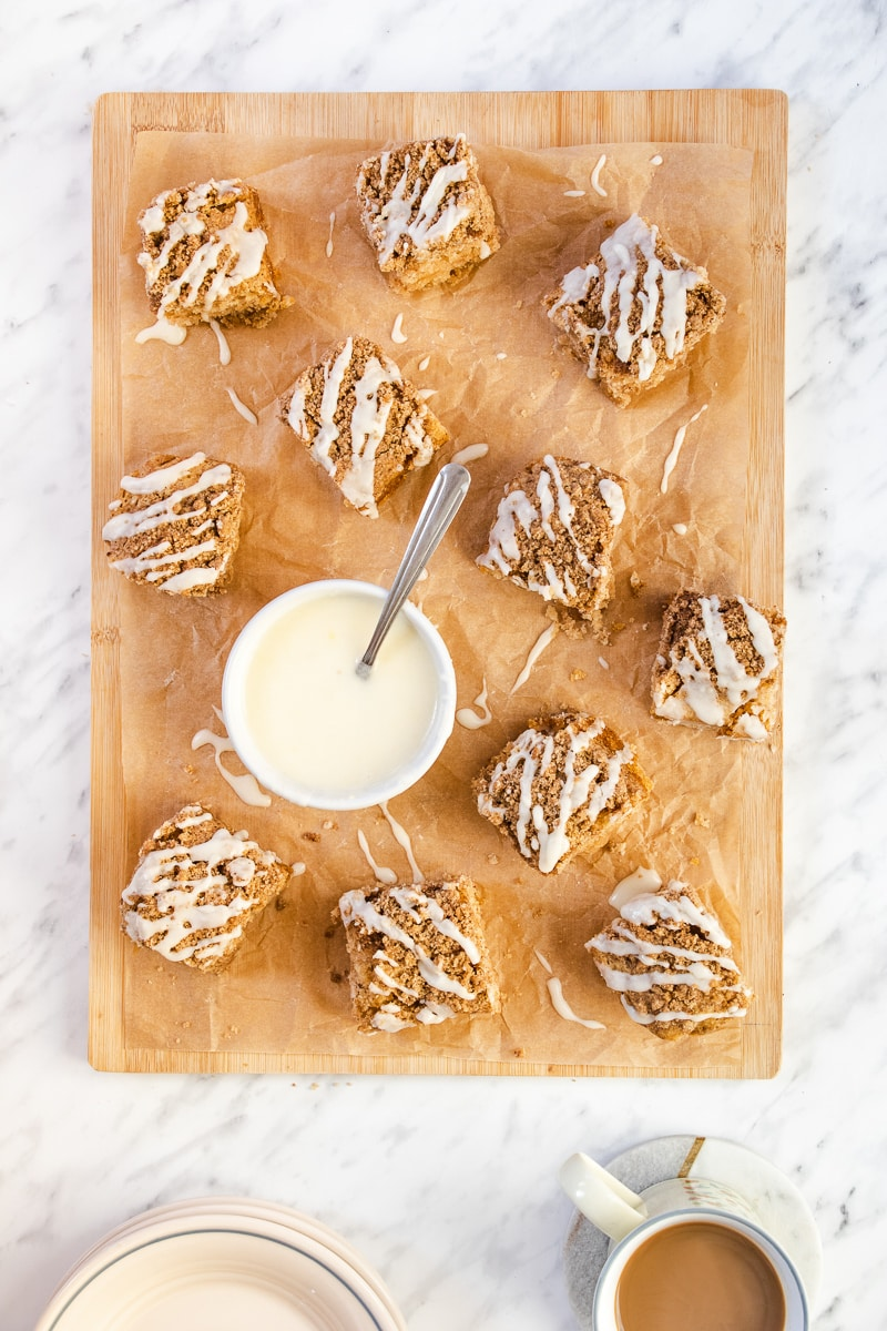 Coffee cake squares on a wooden cutting board with a bowl of white icing