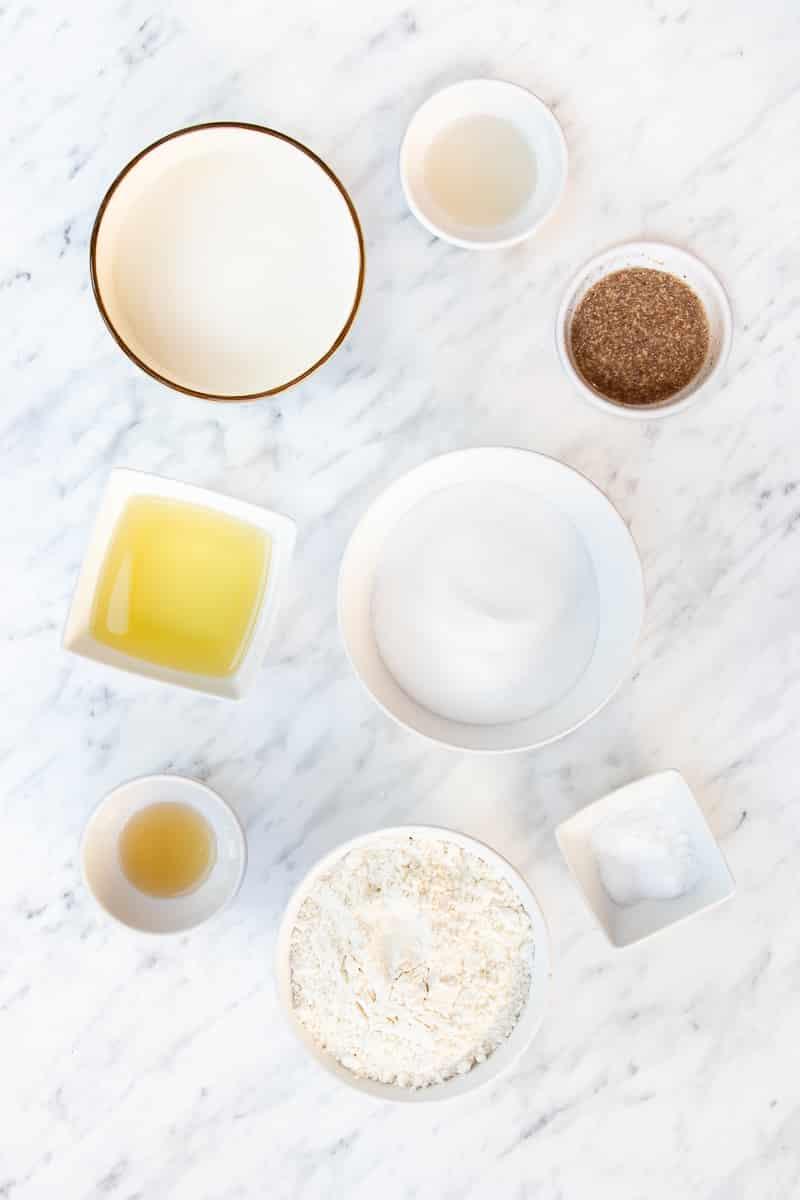 Bowls of sugar, cinnamon, flour, butter, vanilla extract, almond milk, vinegar, and salt on a countertop