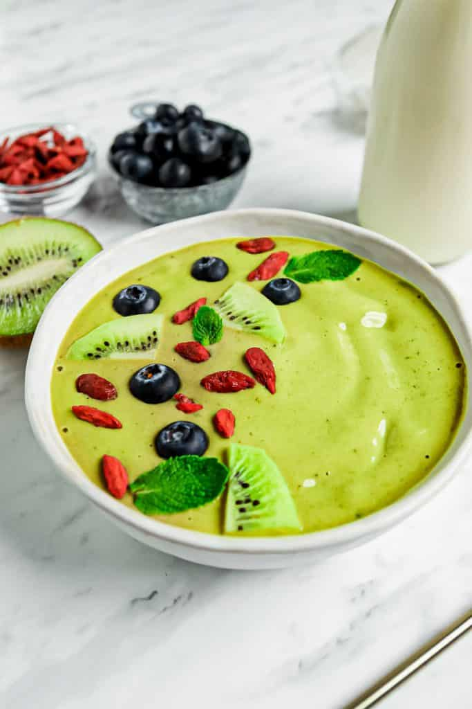 White bowl with green creamy substance in it. Topped with kiwi, blueberry and goji seeds.