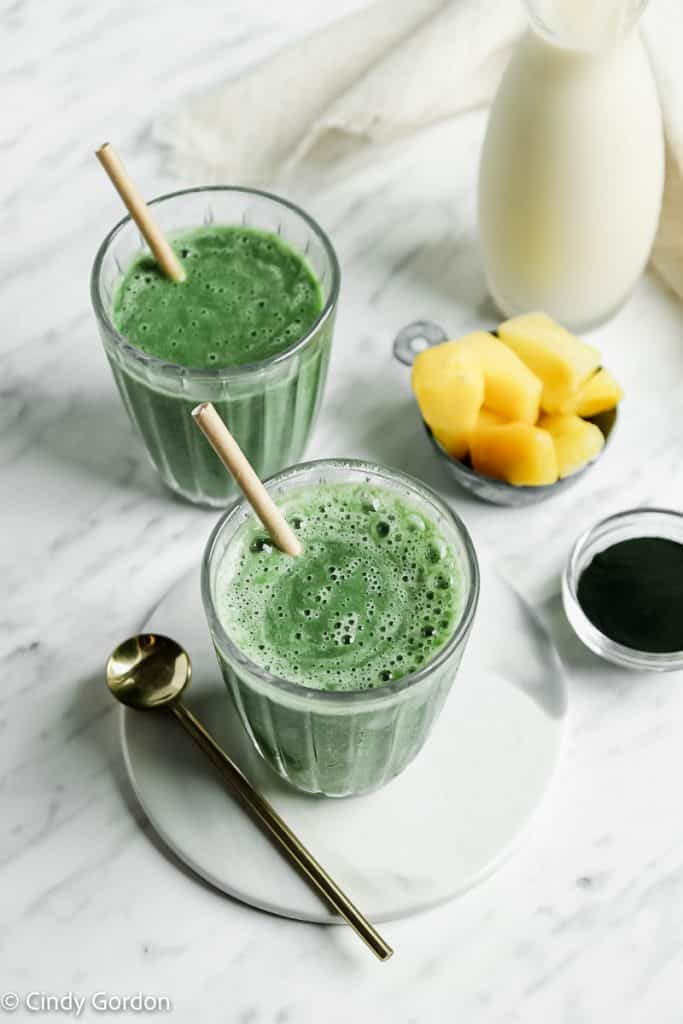 two green smoothies with straws in two tall clear glasses. front glass is on a white plate with a gold spoon