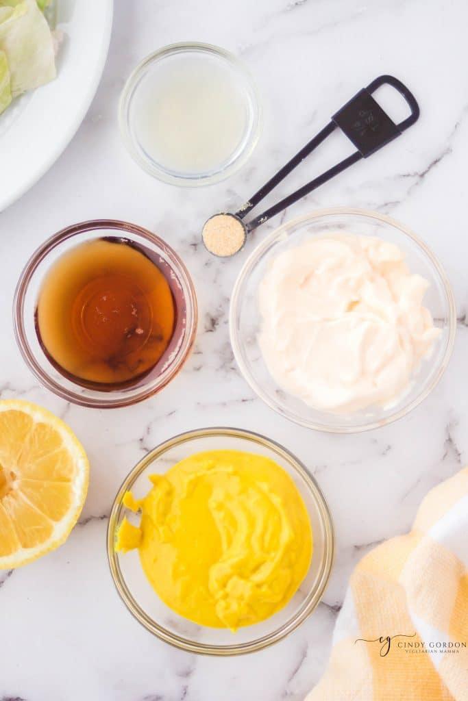 ingredients for vegan honey mustard, each in separate bowls on a marble countertop