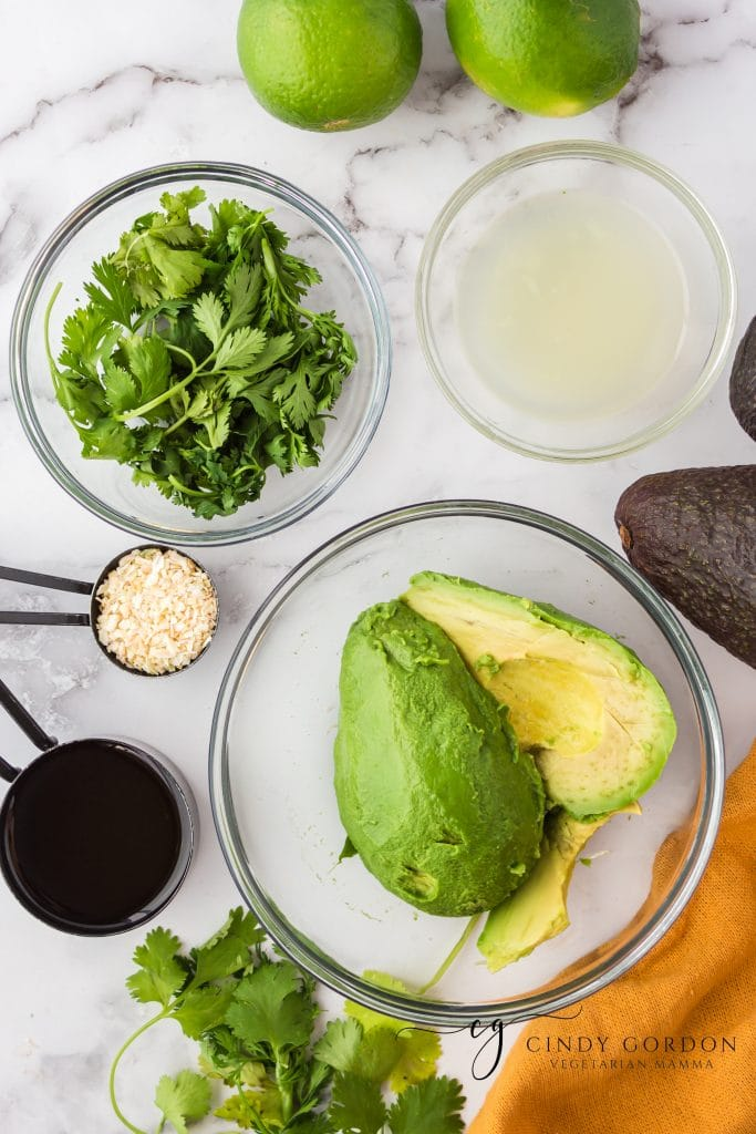 Ingredients for vegan avocado dressing, each in separate bowls on top of a marble counter with an orange towel on the side.