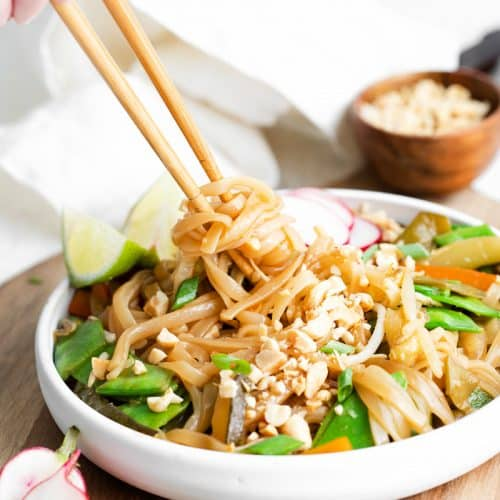 a shallow white bowl filled with vegetable pad thai being eaten with chopsticks. The bowl is on a light wooden cutting board.