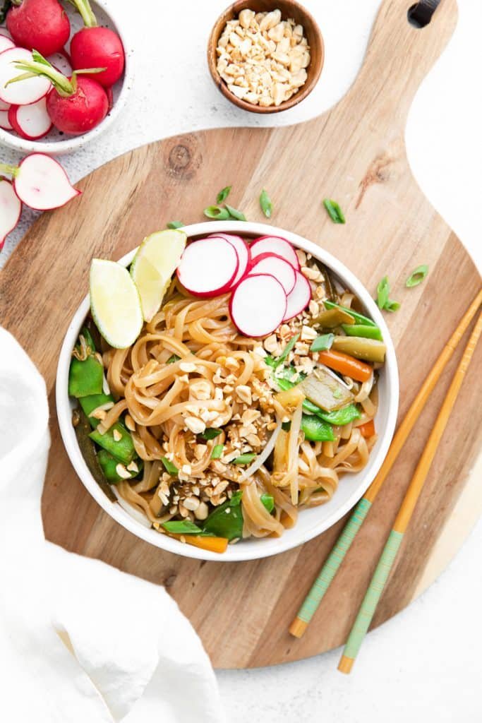 top down view of a wide white bowl filled with pad thai. Garnishes include lime, green onion, peanut, and radishes. The bowl is on top of a wooden cutting board and next to a pair of wooden chopsticks.