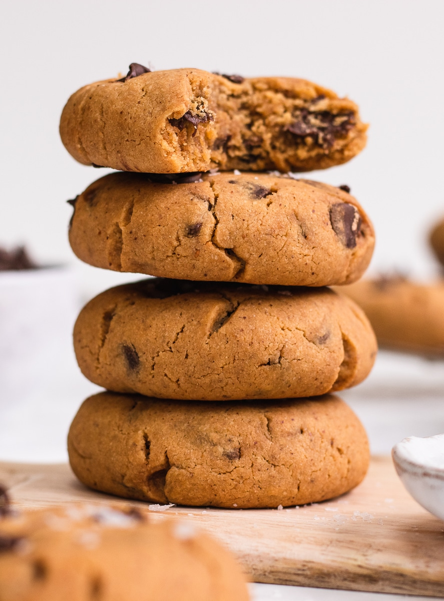 A stack of 4 vegan peanut butter cookies with a bite taken out of the top one
