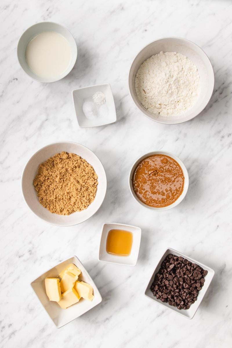Bowls of peanut butter, almond milk, vegan butter, chocolate chips, gluten-free flour, and vanilla extract