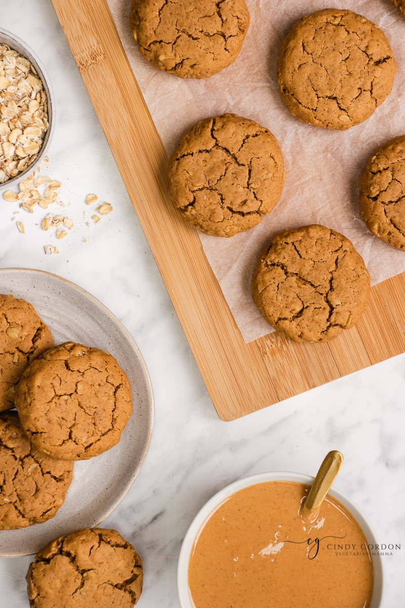 Vegan peanut butter oatmeal cookies on a cutting board and on a plate next to a bowl of peanut butter