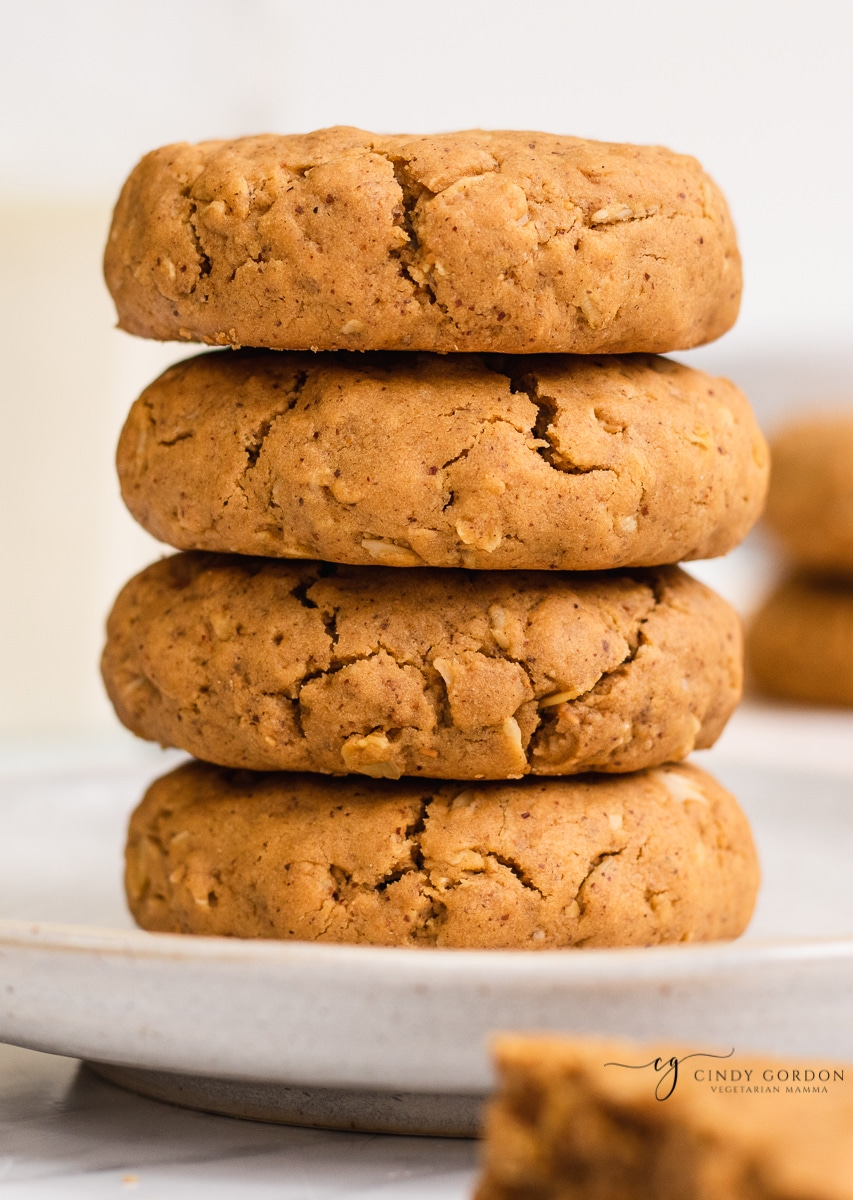 A stack of 4 vegan peanut butter cookies with rolled oats on a cream plate
