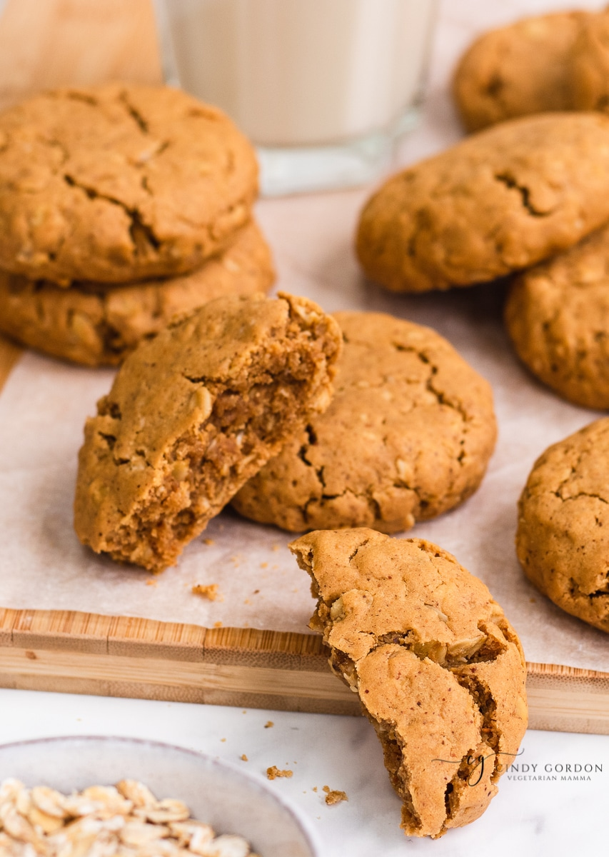 A gluten-free peanut butter cookie split in half next to more whole cookies
