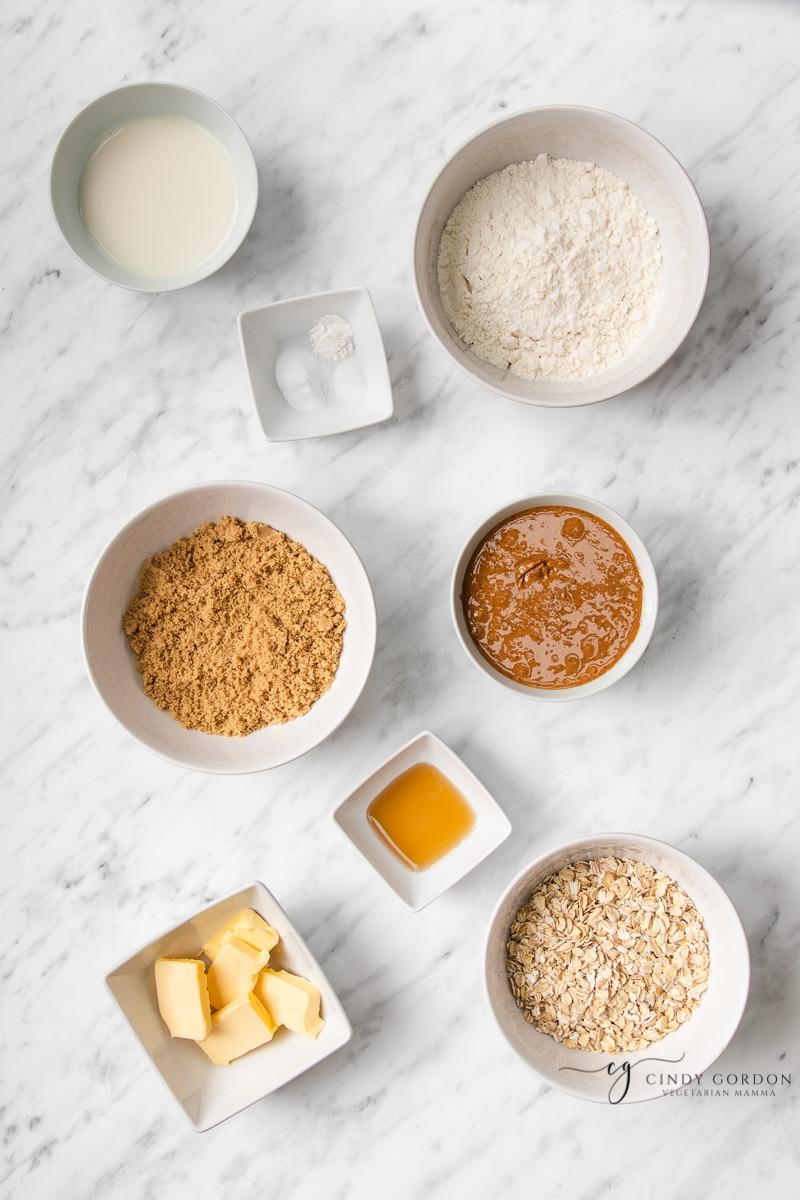 Bowls of gluten-free flour, peanut butter, brown sugar, vanilla extract, almond milk, salt, vegan butter, and rolled oats
