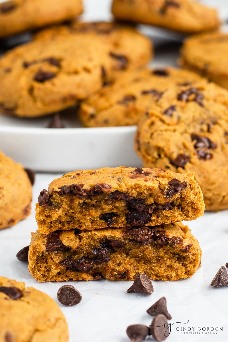 A moist pumpkin and chocolate chip cookie split in half in front of a plate of cookies