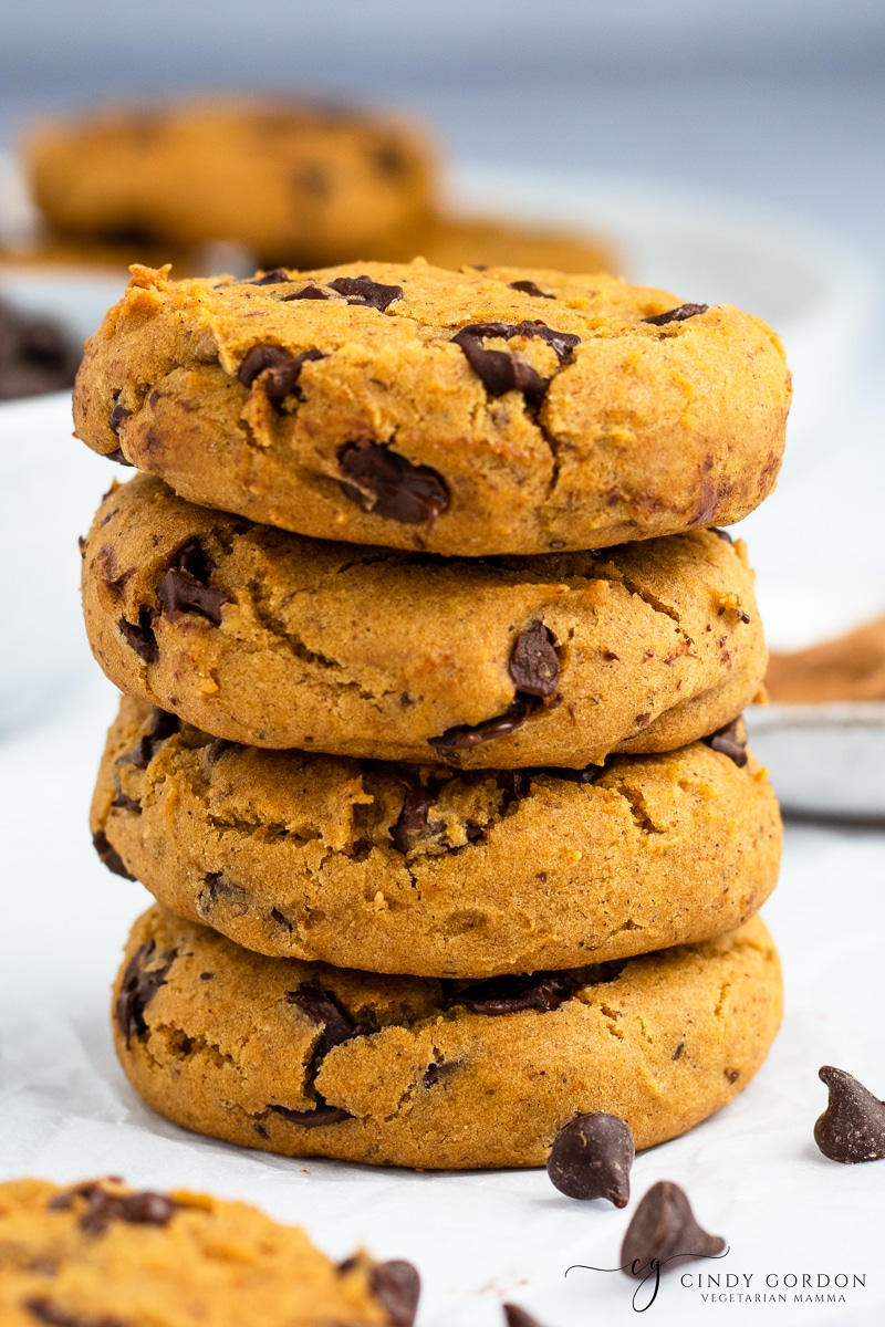 A stack of vegan pumpkin chocolate chip cookies surrounded by dark chocolate chips