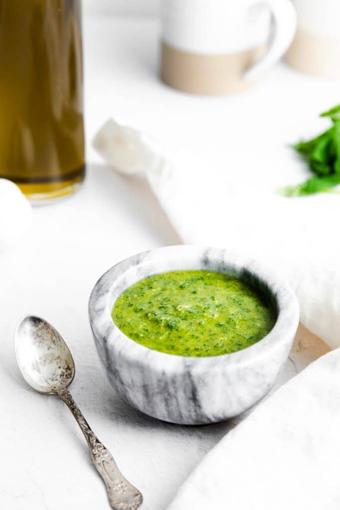 a marble bowl of pesto with a silver spoon next to it.