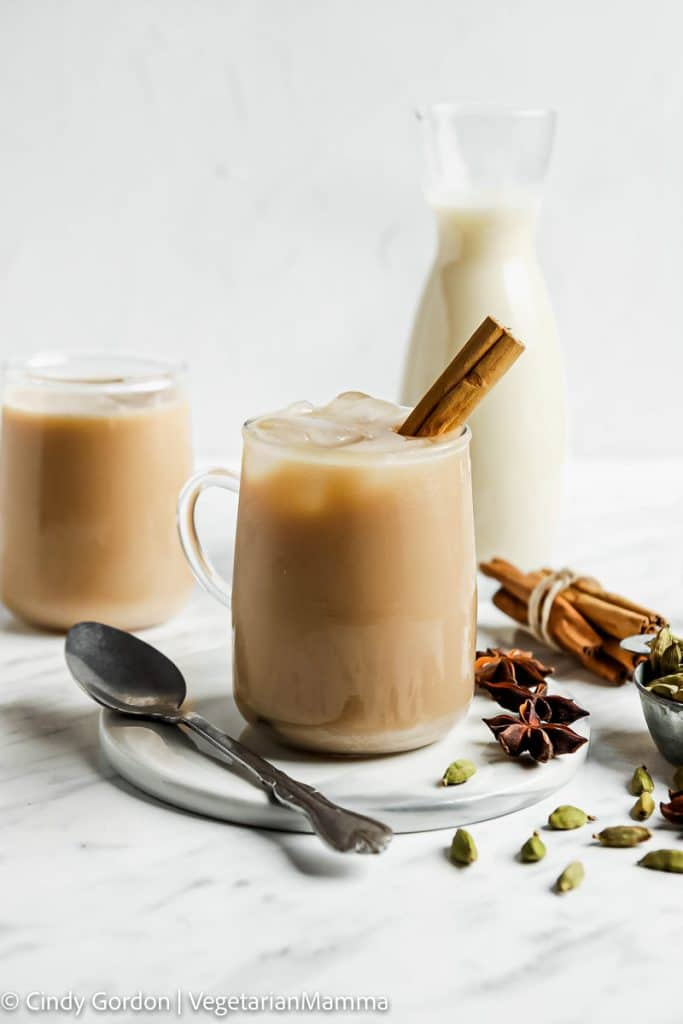 a glass mug filled with an ice chai latte. There is a cinnamon stick in the mug and a glass milk bottle behind it.