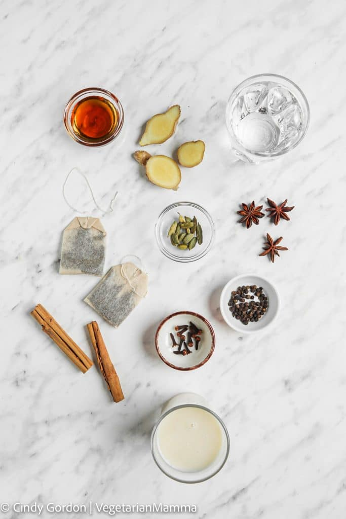 Ingredients for chai latte laid out on a marble countertop