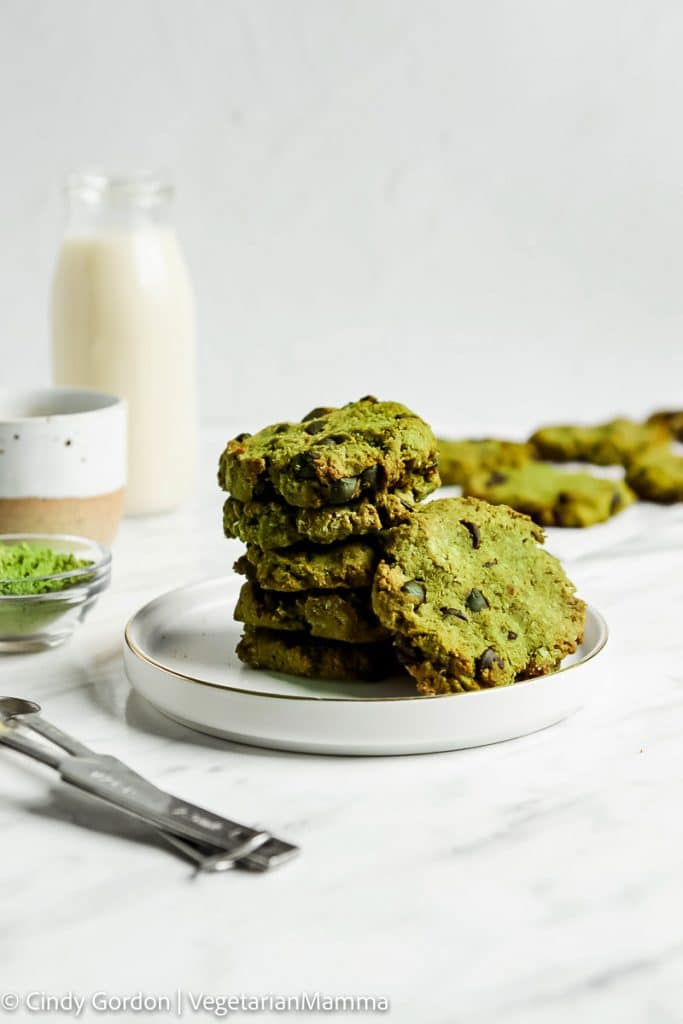 a plate of stacked green chocolate chip cookies on a white plate.