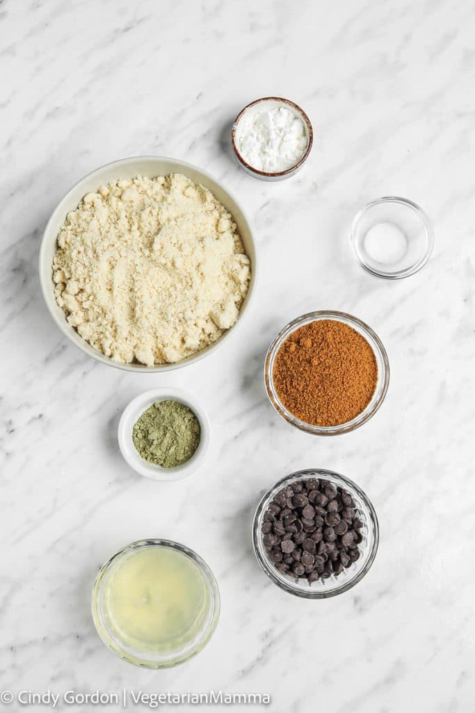 Ingredients for Matcha Chocolate Chip cookies, each in separate bowls on a marble countertop