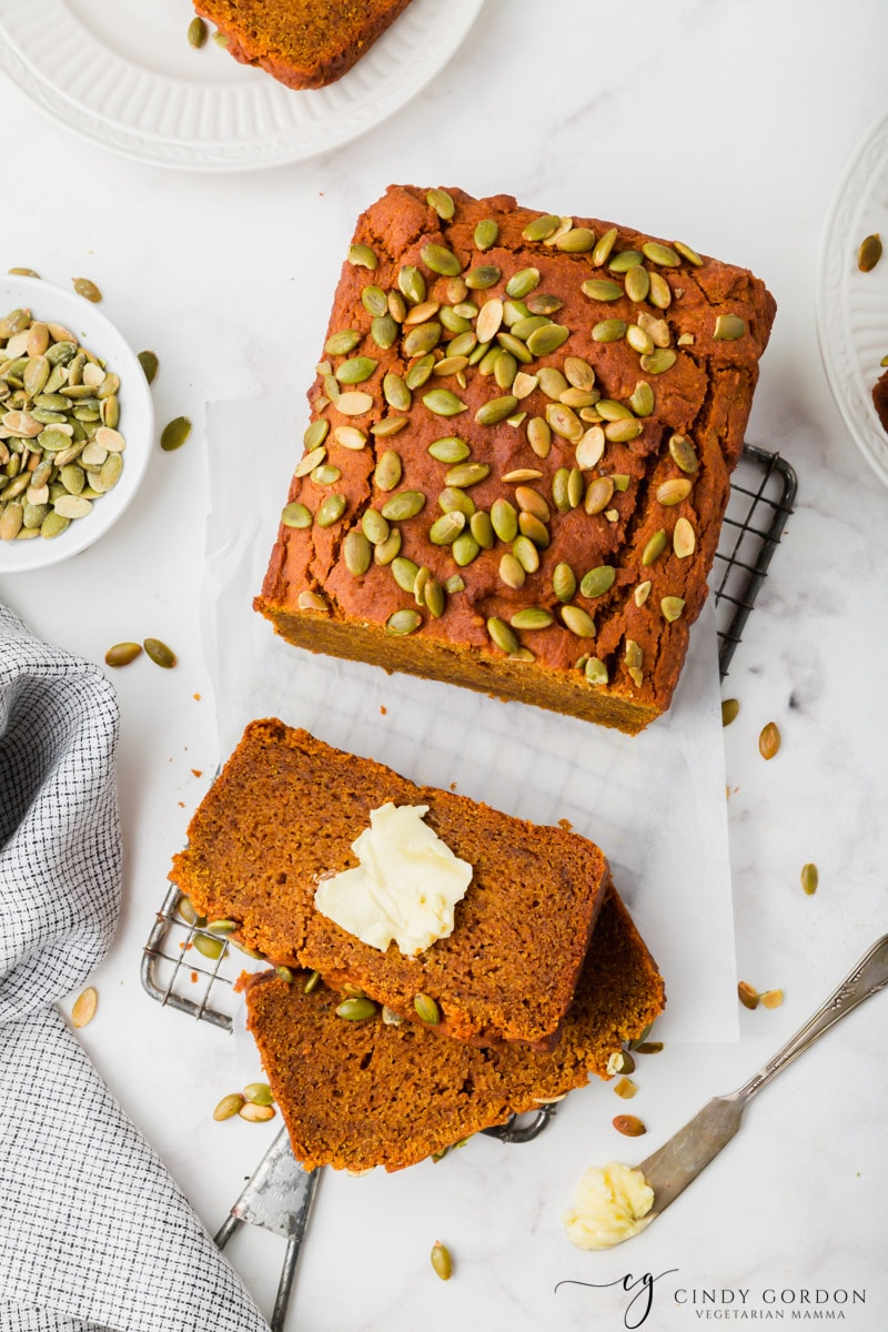 Slices of pumpkin bread with butter next to a loaf of bread garnished with pumpkin seeds