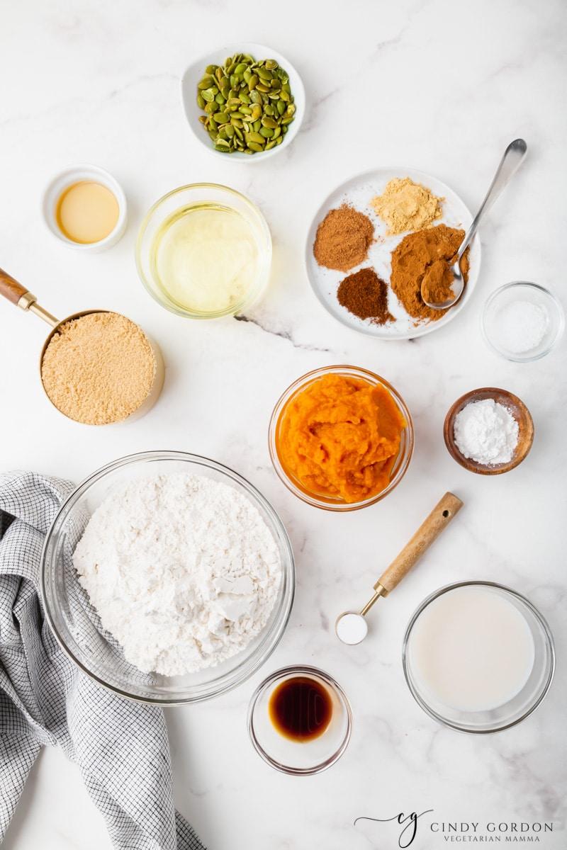 Bowls of flour, pumpkin puree, pumpkin pie spices, baking powder, baking soda, brown sugar, and vegetable oil