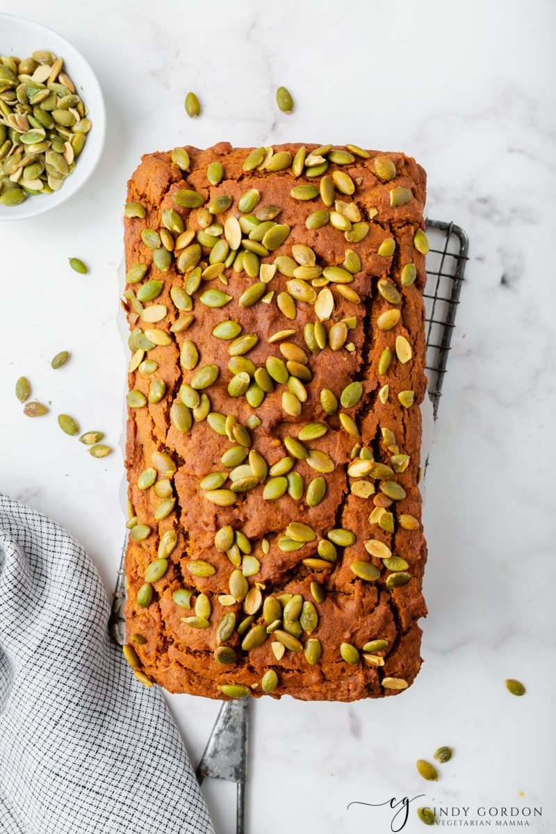 Overhead shot of a loaf of pumpkin bread garnished with seeds on a wire cooling rack