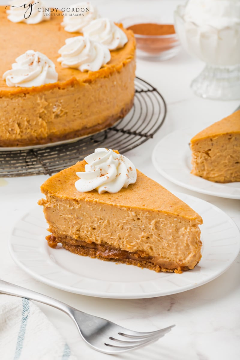 A slice pf pumpkin cheesecake with graham cracker crust on a white plate in front of a whole cake