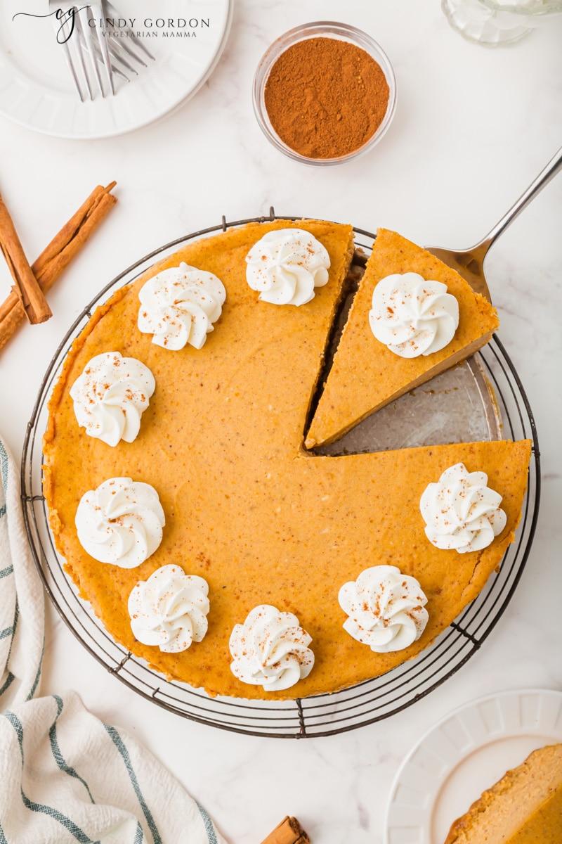 Overhead shot of a vegan pumpkin cheesecake with a cut slice on a spatula