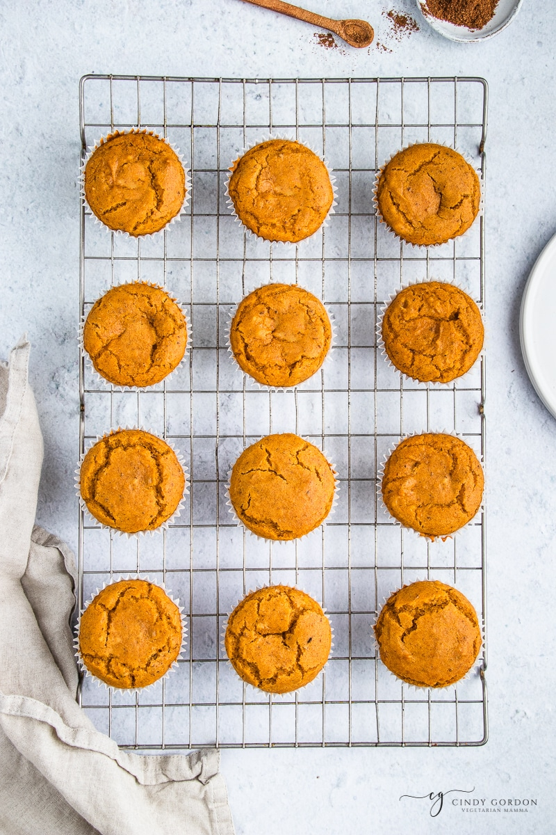 Overhead shot of a dozen pumpkin muffins on a wire rack