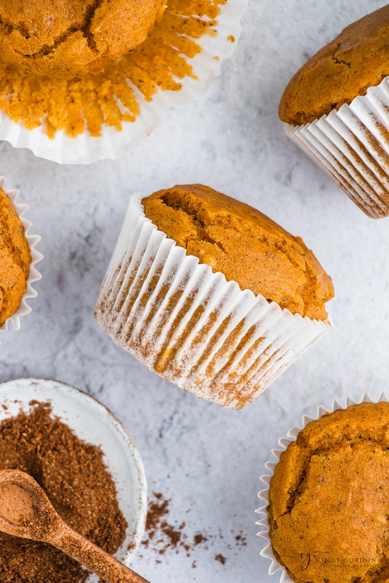 A pumpkin muffin in a white wrapper on its side surrounded by more vegan muffins