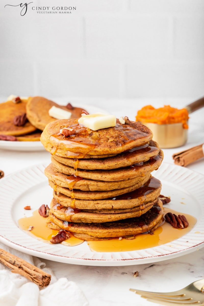 A tall stack of pumpkin pancakes covered with maple syrup and topped with vegan butter