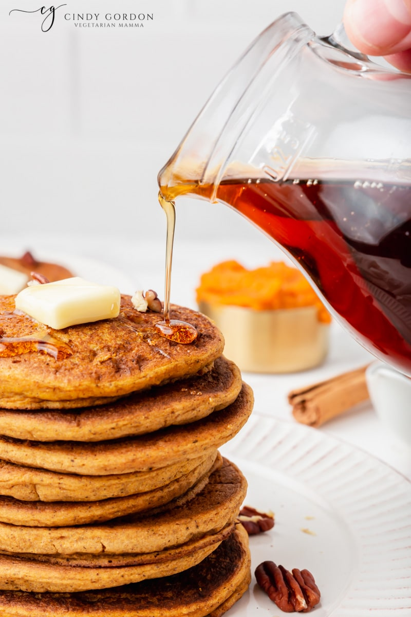 A hand pouring maple syrup over a stack of vegan pumpkin pancakes