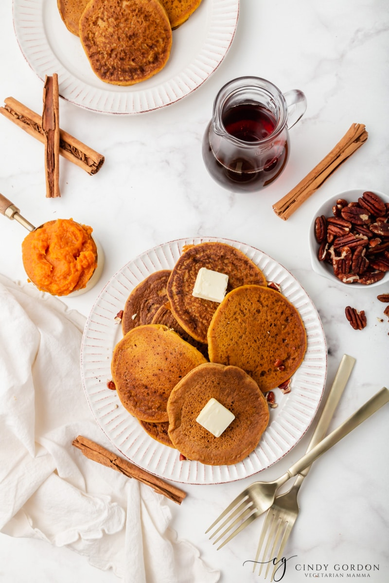 Overhead shot of a plate of pumpkin pancakes surrounded by syrup, pumpkin puree, cinnamon sticks, and pecans