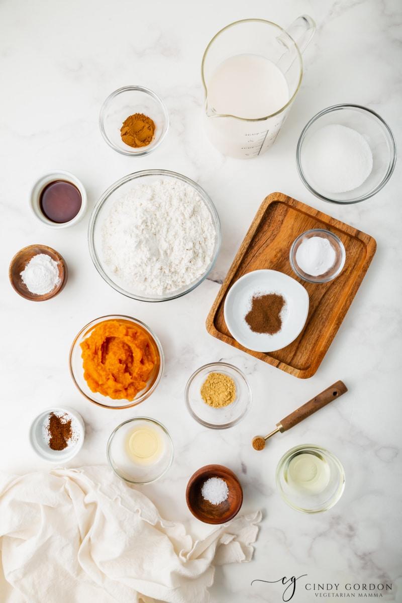 Bowls of flour, milk, sugar, salt, cinnamon, pumpkin puree, cinnamon, nutmeg, ginger, and cloves