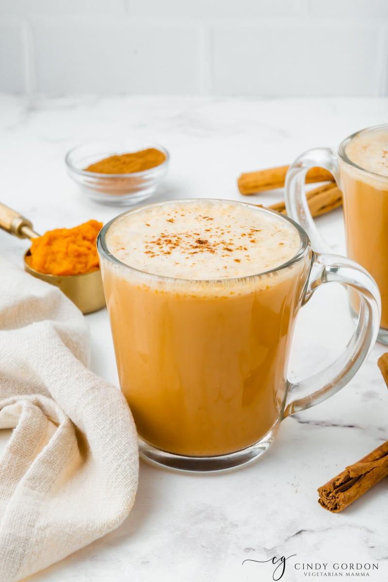 A frothy pumpkin spiced latte in a clear coffee mug surrounded by cinnamon and pumpkin puree