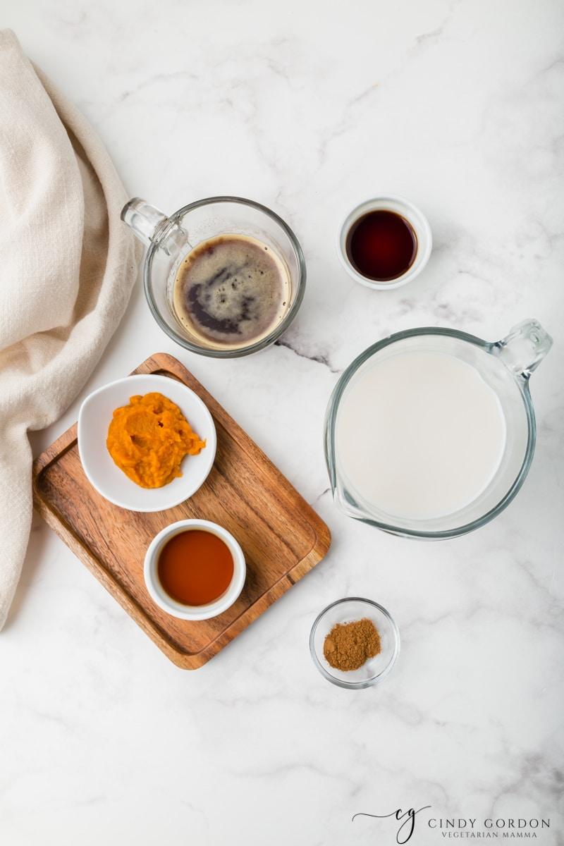 Bowls of non-dairy milk, pumpkin puree, maple syrup, vanilla extract, espresso, and pumpkin pie spice