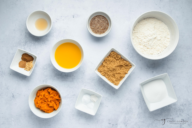 Bowls of gluten-free flour, brown sugar, pumpkin, spices, almond milk, and flax egg