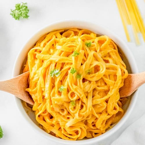 a serving bowl filled with fettucini with pumpkin alfredo sauce.
